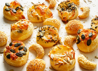 Cheese snacks with puff pastry sprinkled with a mix of seeds on a white background