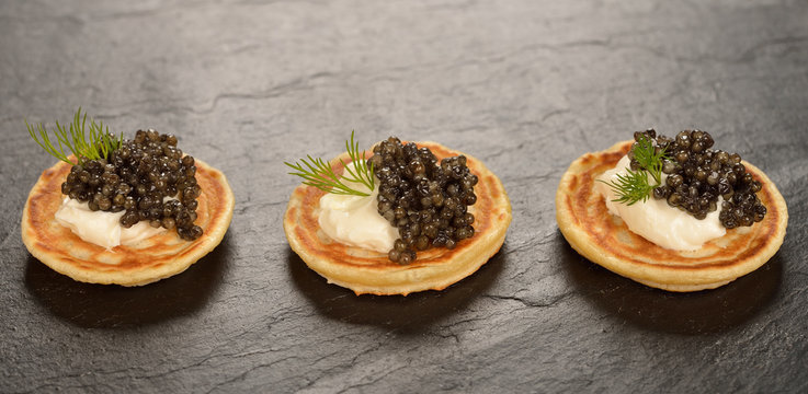 Mini pancakes with black caviar