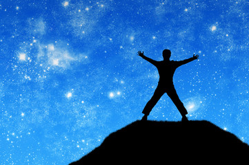 Concept of success. Silhouette of a happy man on the mountain top against the sky with stars