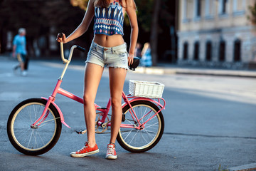 Trendy Hipster Girl with Bike on Urban Background. Modern Youth