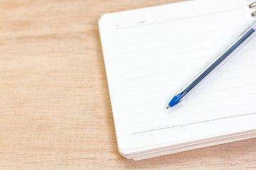 Empty notebook and pen on wooden background
