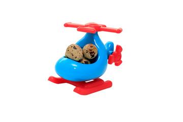 Helicopter delivery of eggs. toy helicopter with quail eggs in the cockpit, isolated on white background