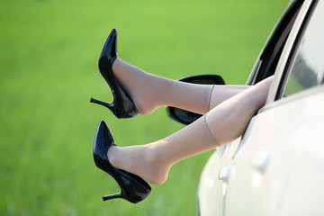 Woman legs out the windows in car with green paddy field backgro