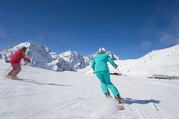 Skiing on skirun in the alps - prepared piste and sunny day