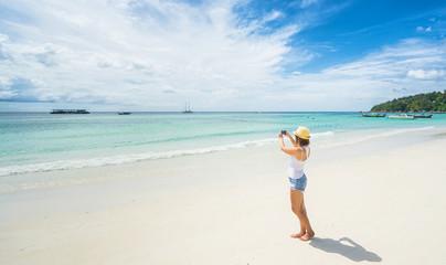 Female tourist taking photo of beautiful island beach on smartphone.