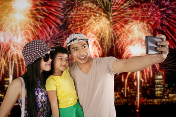 Family taking selfie photo in the fireworks festival
