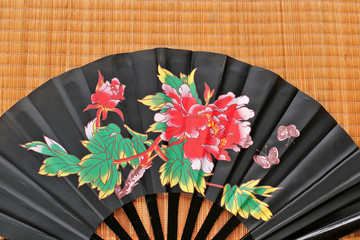 Black Chinese fan on bamboo background