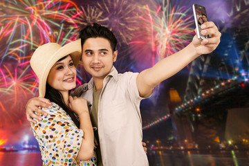 Happy couple taking selfie with fireworks background
