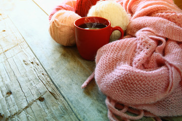 selective focus photo of pink cozy knitted scarf with to cup of coffee and wool yarn balls  on a wooden table. faded style retro filtered