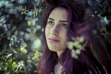 looking melancholic girl in a forest in autumn, red long hair