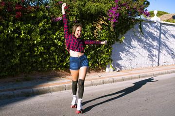 Beautiful cheerful woman on roller skates crying 'Hurrah'