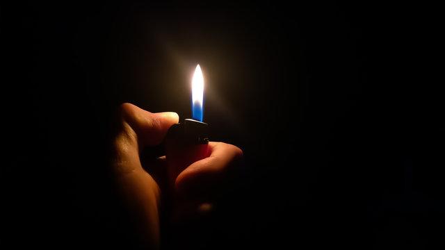 Lighter in a Hand Against Black Backdrop