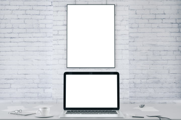 Blank picture frame on white brick wall and blank white laptop s
