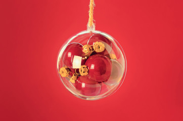 Transparent ball with a red christmas balls inside on red backgr
