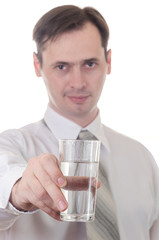 The young man holds the transparent glass with water in hand