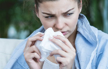 Ill woman blowing nose