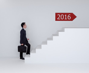Business man stepping up on stairs to 2016