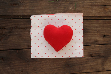 Red heart on polka dot paper and wooden background