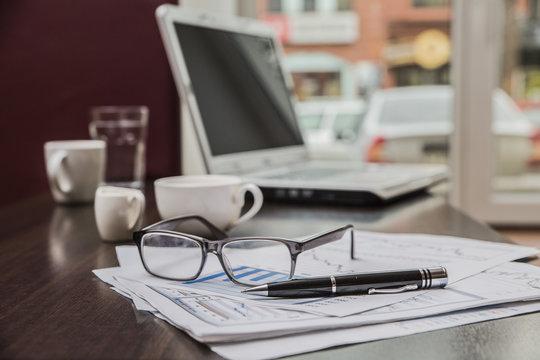 На столе лежат аксессуары для бизнеса: очки, бумаги, ручка, ноут-бук, чашка кофе