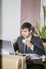 менеджер в деловом костюме работает на компьютере в кафе во время обеда и пьет кофе.