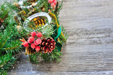 Candlestick and Christmas tree branches on a wooden table