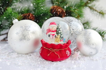 A snow globe with snowman and christmas decorations against the background of fir branches