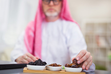 Arabian man takes dried fruits. Focus on fruit