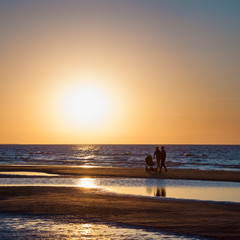 Sea at sunset and silhouettes of family couple with baby carriag