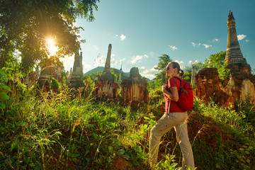 female traveler with backpack walking and looks at sunset among ancient Buddhist stupas. Mayanmar (Birma)