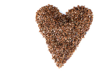 a pile of brown flax seeds in heart shape form on isolated white background
