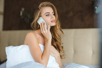 Attractive woman sitting in bed and talking on cellphone