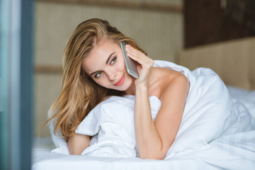 Attractive young woman talking on mobile phone lying in bed