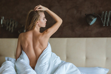 Back view of woman sitting topless on bed