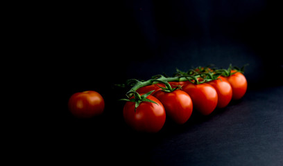 Ripe Red Tomatoes on a Wooden Table with Black Background. Dark Rustic Old Style
