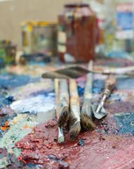 Several brushes lie on the palette