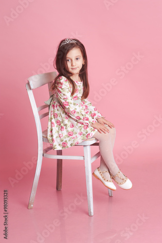 b698434510be Cute baby girl 4-5 year old sitting on white chair over pink in room.  Wearing floral pattern dress