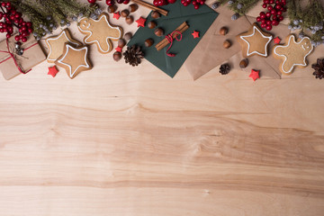 Christmas decoration on wooden background with cookies, fir tree, cinnamon, present and toys. Copy space, top view.