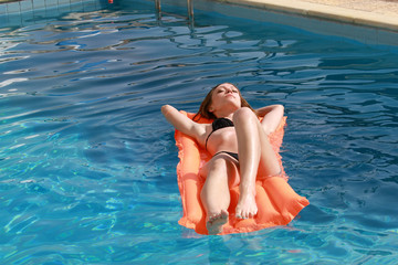 Woman relaxing on an inflatable mattress in pool