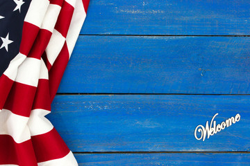 Welcome sign with American flag on antique rustic royal blue wooden background
