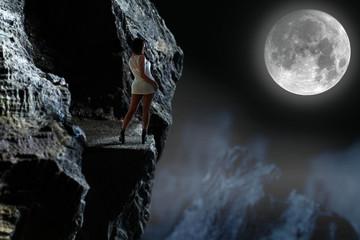 Piękna dziewczyna w górach przy księżycu.