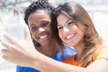 Junge Frau macht Selfie mit afrikanischer Freundin