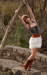 Cute Young Woman in Boots and Skirt Outside