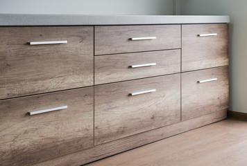 Wooden kitchen drawers with silver handles Wall mural