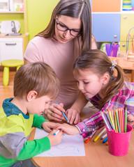 beautiful kids and young female teacher in kindergarten classroom