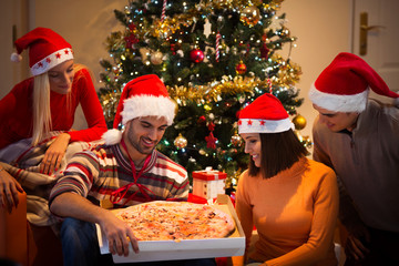 Group of young people having a pizza for New Year's eve dinner party