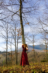 Woman in red dress portrait, autumnal forest