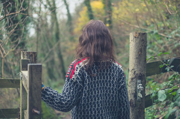 Young woman opening gate in forest