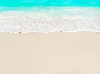Ocean wave and white sand at tropical beach, vacation background