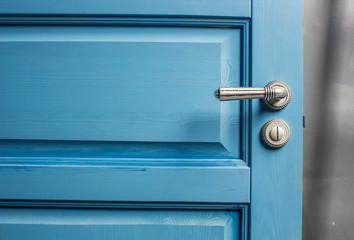 open wooden door painted in blue with a beautiful a metal handle and the castle