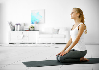 Young attractive woman do yoga exercise in the room